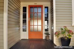 The house's weatherboard exterior is painted in Resene Triple Ash, the windows and trims in Resene Quarter Thorndon Cream and the steps in Resene Double Masala. Bright Front Doors, Orange Front Doors, Orange Door, Exterior Color Schemes, Exterior Paint Colors For House, Colour Schemes, Front Door Porch, House Front, Weatherboard Exterior