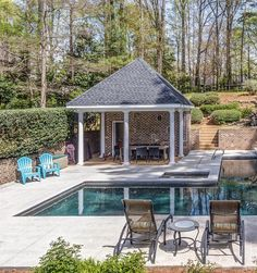 Red brick pool house design with white columns. Covered seating area. Cement patio. Brick walls. Poolside seating. Hot tub. Blue chairs.