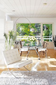 Norman Fosterin ruokapöytä on tuotu pariskunnan Italian-kodista, tuolit löytyivät tästä talosta. Ikkunoita suurennettiin remontin yhteydessä ja terassin umpikaide uusittiin ilmavammaksi. Emäntä ei pidä verhoista eikä halunnut peittää kaunista näkymää sälekaihtimillakaan. Onneksi löytyi Woodblind, joka toimittaa puisia säleluukkuja mittatilaustyönä.