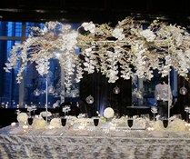 Branches of white orchids hang above an elegant black and white table.