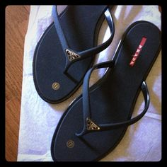 Prada flip flops Black Prada flip flops with the Prada sign in gold on the front and written in red on where your foot steps. never been worn before got them as a present and they were too big! Prada Shoes