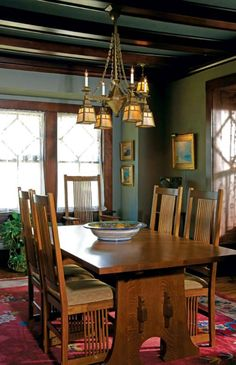 In the dining room, a reproduction gasolier-style fixture hangs over the Stickley dining-room table.