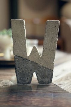 DIY Concrete Letter  Supplies:  Hollow cardboard letter (available at your local craft store)  Box cutter  Breathing mask (or something to cover your nose so you don't breath in concrete dust) Disposable Gloves  2 - Plastic spoons  2 - Disposable Plastic Bowls  1 - Disposable Cup Concrete mix Cement color  Water