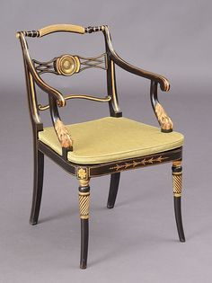 REGENCY EBONIZED, PARCEL-GILT AND CANED ARMCHAIR  With an arched reeded top rail above pierced backsplat centered by a brass lion medallion, the down-swept armrests raised on lion paw supports, above the caned seat, raised on sabre legs. 34 x 21 x 22 in.