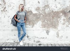 Hipster girl wearing blank gray t-shirt, jeans and backpack posing against rough street wall, minimalist urban clothing style, mockup for tshirt print store