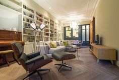 Living room at l'Eixample, Barcelona, designed by FFWD Architects.   Details: Chevron parquet. Built in bookshelves. Eames Lounge Chair and Ottoman.
