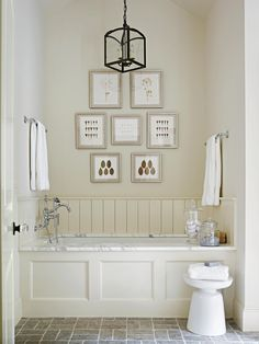 When framing art in the bathroom, a clever trick for a cohesive look is to mat the art in a color identical to the walls. These framed pieces are the perfect beige bathroom accessories to pair with beige walls and wainscoting. #bathroomideas #bathroomcolorschemes #beigebathrooms #bathroomdecor #remodel #bhg