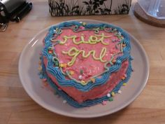 "a fierce looking pink heart shaped cake with blue icing around the trim and star shaped sprinkles all over. in the middle in lime green icing it says, ""riot grrl"" in lowercase cursive."