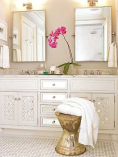 The small, glued-on mirrors add glam to ordinary cabinet doors. in this all-white bathroom. The mirrored drawer fronts also help reflect light.