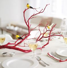 Tree branch spray painted red with birds as a centrepiece.