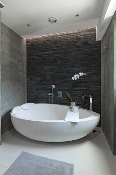 Egg-shaped bath in tight space with stone wall.
