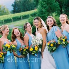 seven bridesmaids wore dresses in different silhouettes, yet kept their look cohesive by wearing the same shade of blue.