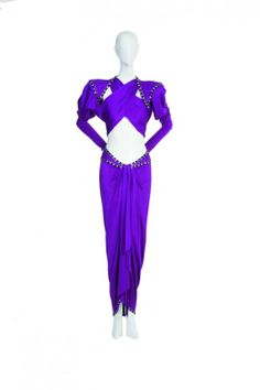 BOB MACKIE CRISS- CROSS GOWN   Cher Circa 1970s purple jersey gown with bare midriff, criss-cross top punched with jet and hematite stones.