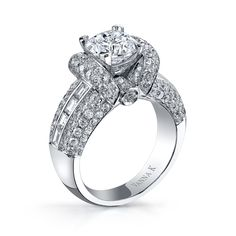 18k white gold diamond engagement ring features a raised collar of pave diamonds that flanks the 3.0 ct. cushion-cut center (not included), and 0.51 ct. t.w. baguettes that line the sides. 1.93 ct. t.w. pave diamonds accent the ring. The Cascade bridal collection represents a promise of eternal love. Vanna K Fine Jewelry is known …