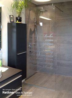 Duschtrennwand in extraweissem Glas mit individueller Beschriftung.