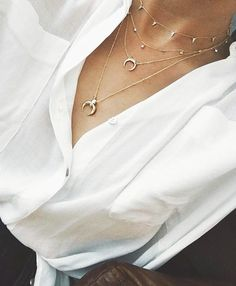 Layered delicate gold necklaces.