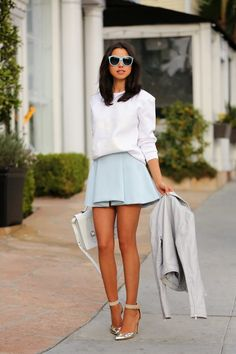 Sky-framed shades w/ matching miniskirt, snowy top, tanned legs & face; snowy purse, concrete jacket