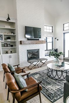Gorgeous modern farmhouse living room designed by Sita Montgomery Interiors - white brick fireplace simple wood mantel leather slingback chairs layered rugs circular coffee table and sconce lighting above open shelving - April 27 2019 at Design Living Room, Family Room Design, Living Spaces, Living Room Brick Wall, Living Room Bench, Brick Wallpaper In Living Room, Leather Living Room Chair, Living Room Fire Place Ideas, Armchair Living Room