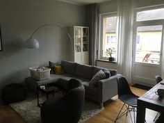 Modernes Wohnzimmer mit Parkettboden, dunkelgrauer Couch, grauem Flauscheteppich und breiter Fensterfront.  Wohnen in Stuttgart.  #Stuttgart #Wohnen #Wohnzimmer