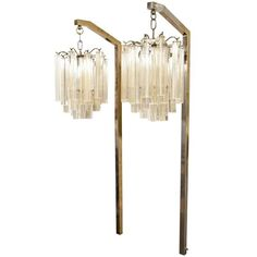 A vintage pair of Venini pendant sconces composed of clear glass rods infused with gold inclusions suspended from brass wall mounts.
