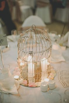 Candles in a birdcage for a wedding centerpiece