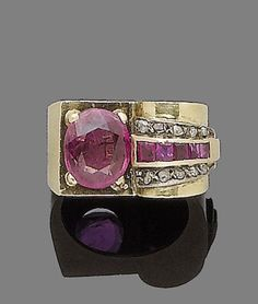 A 1940s ruby and diamond dress ring.  Set with an oval-cut ruby, to a scrolling shoulder channel-set with calibré-cut rubies and rose-cut diamonds, ring size I½ (leading edge)