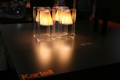 Kartell Light Air Lamp, Light-Air Table Lamp.  The Light-Air Lamp, designed by Eugeni Quitllet for Kartell, seems to defy the laws of gravity. Its 'floating' diffuser creates a memorable illusion, made possible by its transparent rectangular polycarbonate frame which is laser welded together, encasing a conical parabola, This is available in three colors. http://www.stardust.com/SEARCH.html?q=kartell+light+air