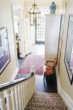 This entry way is warm and inviting. The checkerboard floor and door are gorgeous. I particularly love the red rug and the different sized art.