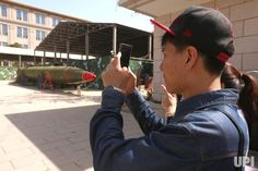 Chinese tourists look at weapons on display outside the temporarily closed Chinese Military Museum of the People's Revolution in Beijing on…
