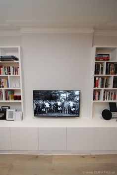 These are contemporary style media wall units built from scratch in London UK by EMPATIKA.uk They are built into alcoves and the base units fit in front of the chimney breast to make a really striking media unit which would not have been the same if there were just units in each alcove. The base units act as a kind of supporting plinth that hold up the bookshelves and highlight the TV. http://EMPATIKA.uk