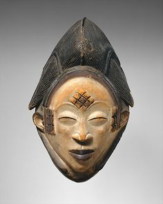 """Mask (Mukudj)   Punu peoples   The Met The creator of a """"mukudj"""" mask would attempt to capture the likeness of the most beautiful woman in his community. Mask (Mukudj) Date:19th–20th century Geography:Gabon, Ngounié River region Culture:Punu peoples"""