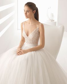 Princess-style beaded lace and tulle wedding dress with V-neckline, sheer inserts and full skirt, in natural/nude. 2018 Rosa Clará Collection.