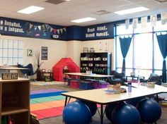 A large, studentless classroom, with large blue bouncy balls, sofa chairs, folding chairs, a tent, crates, mats, and other unique furniture.