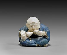 Finely carved and polychromed, figural ivory netsuke; of a seated actor drinking sake, an Okame mask hung from his neck to the back, with a pipe and tobacco pouch, signed Ichiro