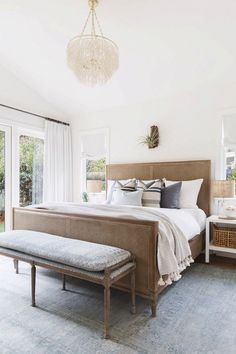 Serene bedroom with white walls, a shell chandelier, and bedding layered with capiz shells, raffia, burlap, and linen