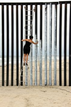 PERFORMANCE ART  'Erasing the Border Mexico/USA' (2016). Ana Teresa Fernández erases a portion the U.S.-Mexico Border fence with blue paint
