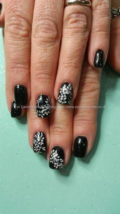Black gel polish with white freehand flower nail art