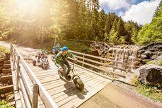 Mountain Cart? Das ist so in etwa wie Gokart/Kettcar fahren unter Ausnutzung von Bergbahnen, damit man nur bergab fahren kann. Das Gerät hat keinen Motor und nur 3 Räder, was für die Fahrt über die vorgesehenen Forstwege ideal ist. Die Fahrt macht kleinen wie großen Piloten einen Riesenspaß und ist ein MUSS für alle, die FAHRZEUGE mögen.   #Gutwettertipps Go Kart, Garden Bridge, Outdoor Structures, Motor, Fly Traps, Gifts For Employees, Gifts For Travelers, Sports Activities, Karting