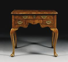 A George I walnut lowboy circa 1720 with quarter-veneered feather and crossbanded top, one long drawer and two short drawers, with shaped apron on cabriole legs and pad feet