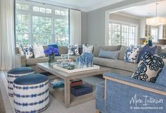 Blue and gray living room features a gray velvet sectional lined with blue pillows facing a gray wash coffee table and a pair of white and blue round stools.