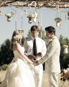 The couple wed under a ceremony arch adorned with rustic branches and hanging jars