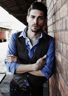 dark grey cotton vest, blue shirt, brown belt, dark denim jeans
