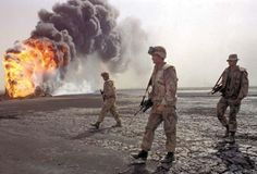 A U.S. Marine patrol walked across the charred landscape near a burning oil well during perimeter patrol near Kuwait City at the end of the Persian Gulf War.