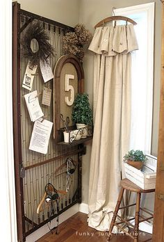 A woodsy antique hanger with weathered clothespins, painter's drop cloth then trimmed with twine and buttons... rustic curtains! Dare you trim your consignment or resale shop windows with these, asks TGtbT.com