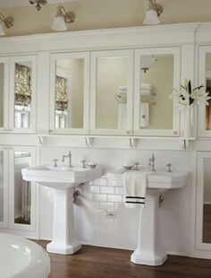 Mirrors in a Cottage Bath If your bathroom doesn't have depth, create it with mirrors. This wall of mirrors doubles the perceived space and reflects natural light while hiding an abundance of built-in storage. Pedestal sinks keep the floor open. Note the shallow ledge above the sinks: a perfect substitute for a counter.