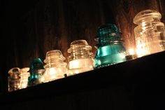 Antique glass insulators lighted with tea candles at night
