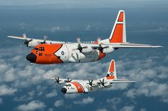 A C-130-H displaying an historic color scheme to commemorate the 50th anniversary of the C-130 in Coast Guard Service, flies in formation with a new HC-130J from Air Station Elizabeth City.