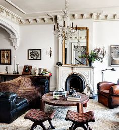 Tour the Most Beautiful Townhouses with Modern, Eclectic Style// crystal chandelier, tufted leather sofa, leather club chair, crown molding, woven stools