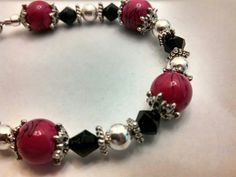 SOLD..  Hot pink glass beads, black crystals and metal findings.  Adjustable clasps.  $15.