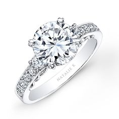 Brides.com: Engagement Rings Under $10,000. Style NK26641-W, Renaissance collection channel-set diamond encrusted shank enagement ring , $7,000, Natalie K  See more round-cut engagement rings.